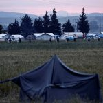 Riot policemen walk amidst tents during a police operation at a refugee camp at the border between Greece and Macedonia, near the village of Idomeni
